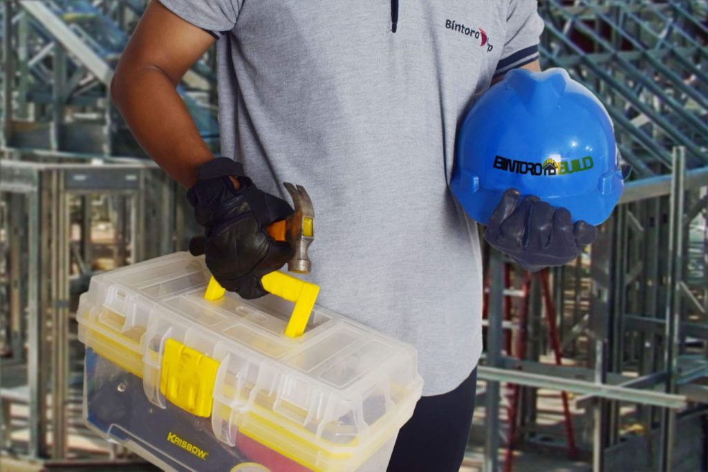 Man from Bintoro Build carrying a tool box and safety helmet