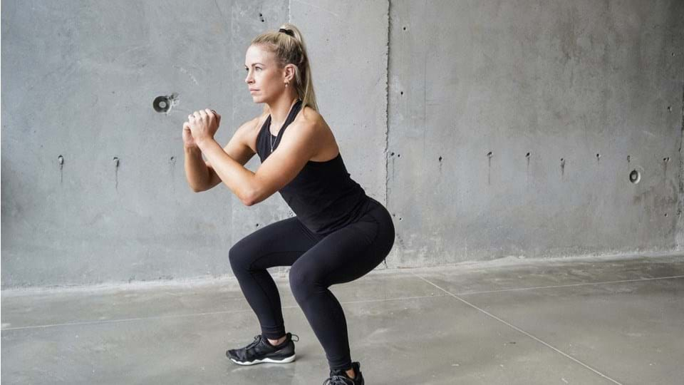 woman doing bpdyweight squats