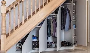 a walk-in closet under stairs
