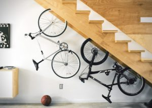 Hanging a bike under the stairs is a good option to maximize unused space.