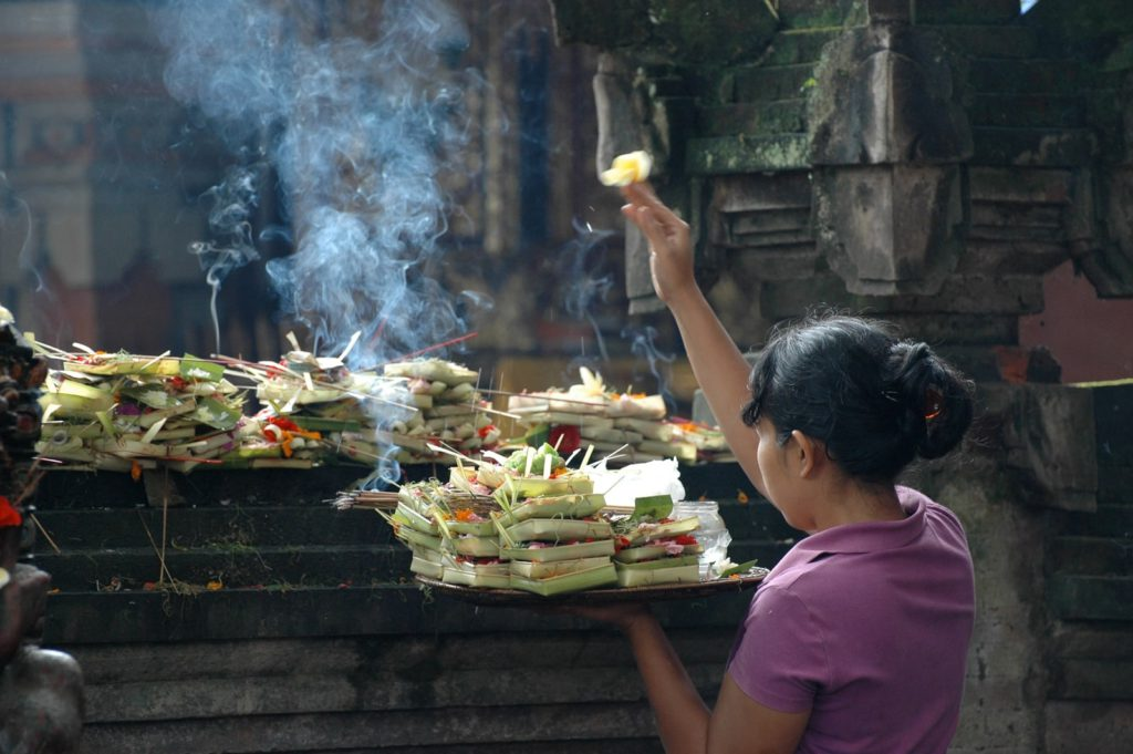 praying during canang sari process